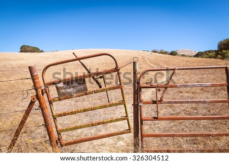 California landscape of rolling hills pasture ranch land with a rusty old gate ajar in the foreground. Path up the hill. Old sign says Please Close Gate. Clear blue sky with copy space - stock photo