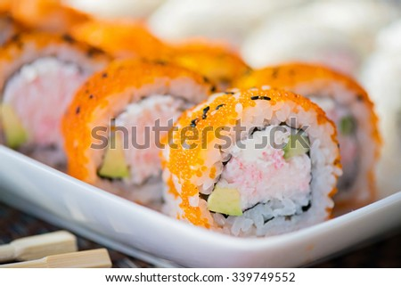 California maki sushi with masago. Roll made of crab meat, avocado, cucumber and masago. Shallow depth of field.  - stock photo