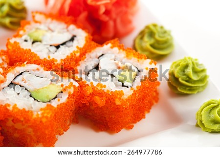 California Maki Sushi with Masago  - Roll made of Crab Meat, Avocado, Cucumber inside. Smelt roe outside - stock photo