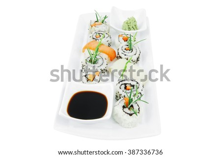California Roll with Avocado and Salmon, Cream Cheese and Raw Salmon inside. on long white plate . isolated over white background . Maki Sushi and Sashimi - stock photo
