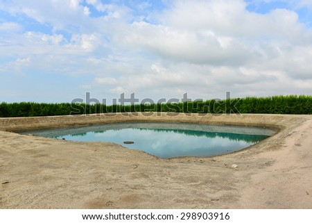 California's four year drought is reflected in the low water level in this Central California irrigation pond servicing nearby orange groves. - stock photo
