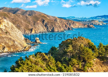 California scenic coastal cliffs along the Pacific Ocean with the city of San Francisco in the background. Blue sky with drifting clouds. - stock photo