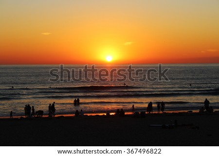 California sunset with people silhouetted against the sea - stock photo
