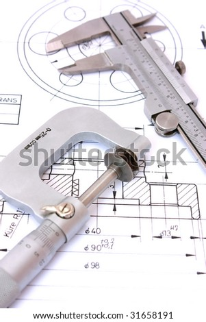 Caliper and Micrometer on blueprint vertical. Shallow depth of field. - stock photo