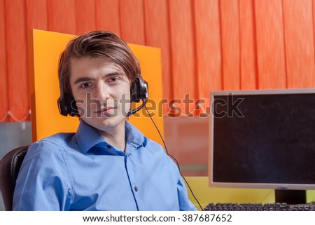 Call center agent at work in his box office - stock photo