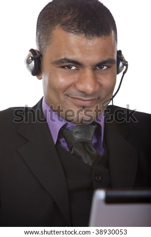 Call center agent wearing a headset and sitting in front of his laptop. Isolated on white. - stock photo