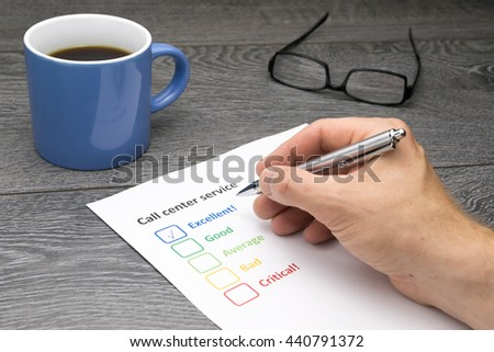 Call center offering excellent service. Customer filling out survey form while having a coffee - stock photo
