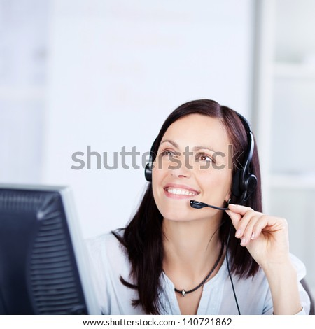 Call center operator with headphone looking at something - stock photo