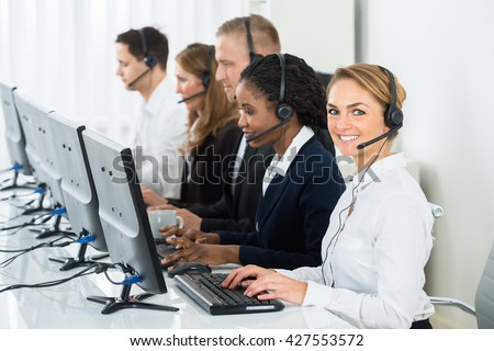 Call Center Operators In A Row Working On Computers In Office - stock photo