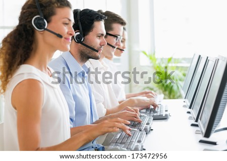 Call center operators working at desk in office