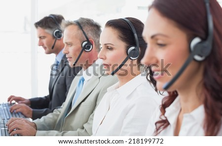 Call center workers wearing headsets and using computers - stock photo