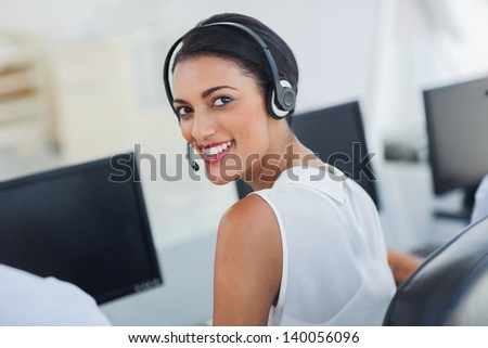 Call centre agent looking over shoulder with her headset - stock photo