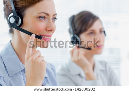 Call centre agents at work and smiling - stock photo