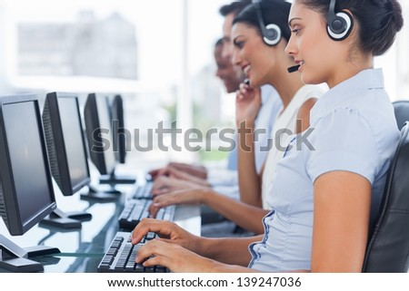 Call centre workers sitting in line while helping people on computers - stock photo