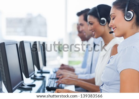 Call centre workers working in line with their headsets - stock photo