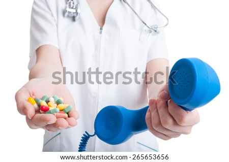 Call for pills concept with woman hands holding phone and multicolored pills.  Contact clinic or medical staff concept - stock photo