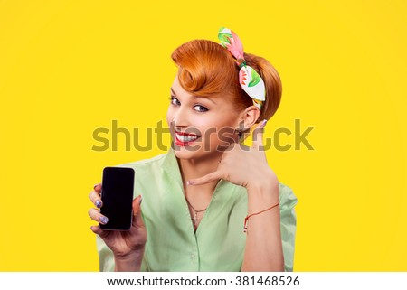 Call me. Closeup red head young woman pretty smiling pinup girl green button shirt holding phone showing call me sign hands gesture looking at you camera, retro vintage 50's hairstyle. Body language - stock photo