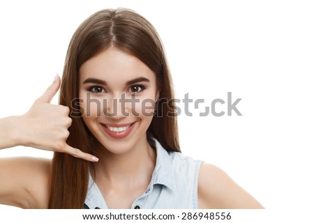 Call me maybe. Portrait of a young beautiful girl with long brown hair wearing blue denim blouse, smiling and holding her hand like a phone hinting calling, isolated on white background