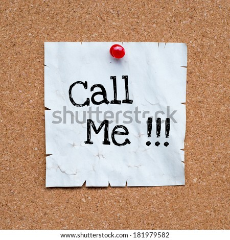 Call me, written on an white sticky note pinned on a cork bulletin board.  - stock photo