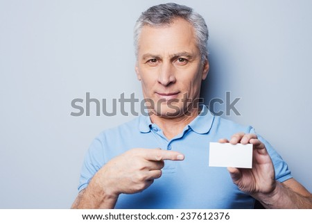Call this number! Handsome senior man pointing on a business card and smiling while standing against grey background
