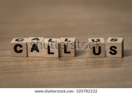 Call us written in wooden cubes on a desk