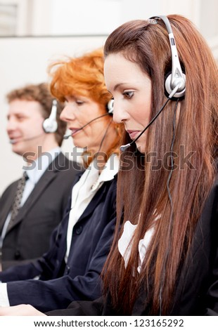 callcenter service team talking with headset workplace with computer - stock photo