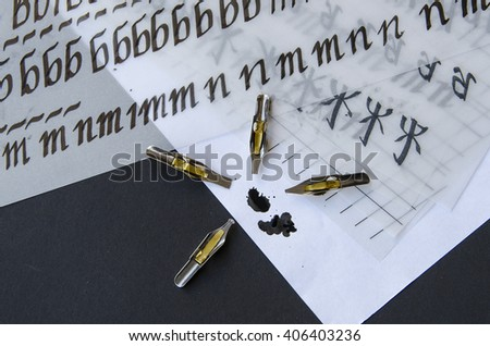 calligraphy pen tips , flat tipped nib, ink stains and practice sheets on the table - stock photo