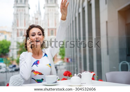 Calling the waiter. Attractive young brunette woman talking on mobile phone while sitting in cafe outdoors. - stock photo