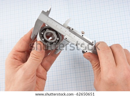 callipers with  bearing in hand on a background of graph paper