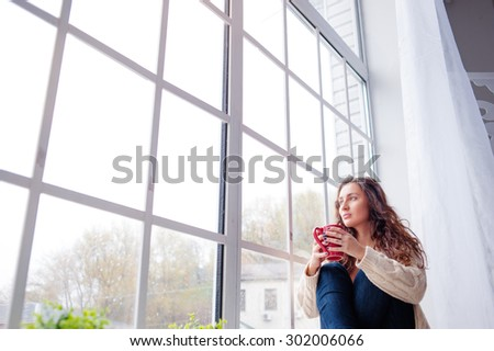 Calm and coziness. Beautiful young woman with cup of tea sitting near the window at home - stock photo