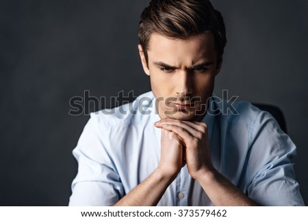 Calm and handsome. Portrait of handsome young man keeping hands clasped and looking thoughtful while sitting against black background - stock photo