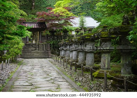 Calm and peaceful green Japanese garden with small stony statues, steps and temple as a symbol of harmony, balance  and relaxation - stock photo