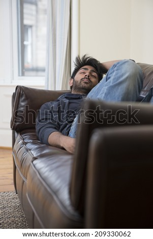 Calm Asian man sleeping on couch at home.