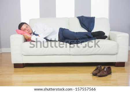 Calm attractive businessman lying on couch after work at home - stock photo