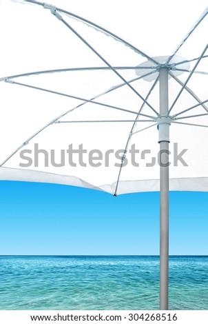 Calm beach scene with white sunshade near the blue sea - stock photo