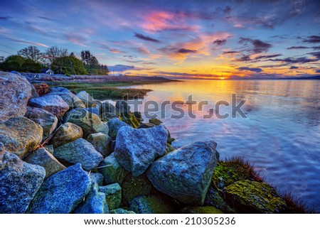 Calm blue river sunset with distant mountains and colorful clouds - stock photo