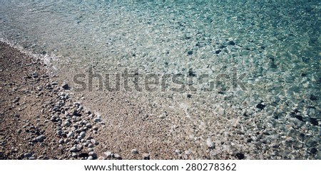 Calm blue sea and pebble shore. Aged photo. Beach at Adrasan, Antalya Province, Turkey. Vintage effect image. Pebble coast. Toned photo. Wide photo for site slider. - stock photo