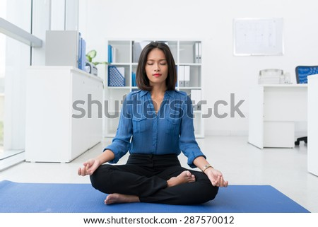 Calm brunette businesswoman practicing yoga in office - stock photo