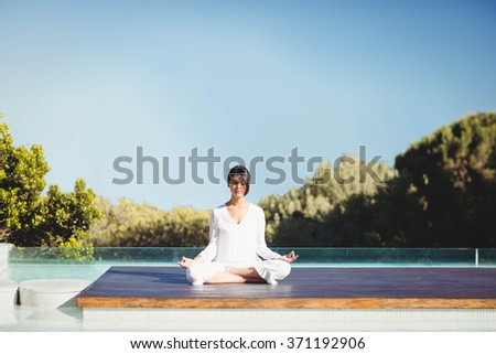 Calm brunette doing yoga by the pool - stock photo