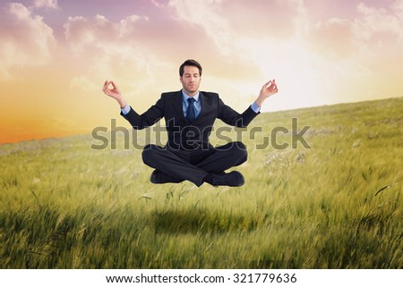 Calm businessman sitting in lotus pose against nature scene
