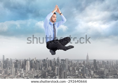 Calm businessman sitting in lotus pose with hands together against cityscape
