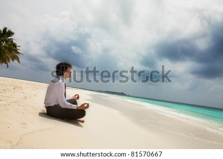 Calm businessman sitting on the shore on the white sand - stock photo