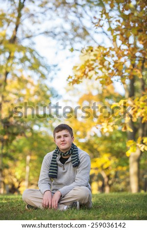 Calm Caucasian teenager sitting on grass during the  autumn season - stock photo
