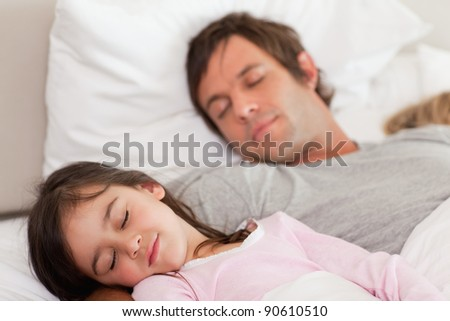 Calm father sleeping with his daughter in a bedroom - stock photo