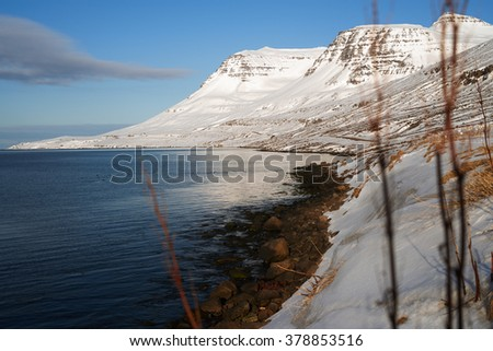 Calm fjord waters with dramatic icy snow covered mountains, beautiful winter landscape - stock photo
