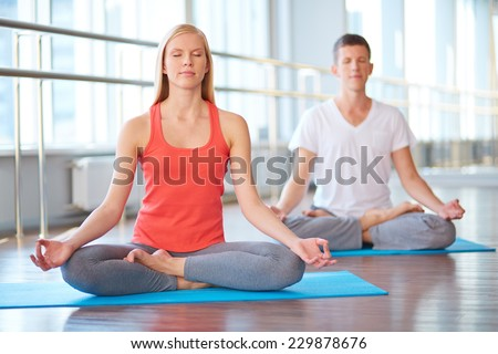 Calm girl and guy doing yougs exercise for relaxation - stock photo