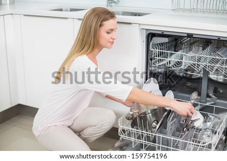 Calm gorgeous model kneeling next to dish washer in bright kitchen - stock photo