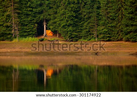 calm high mountain lake at sunset and single orange tent on the beach  - stock photo