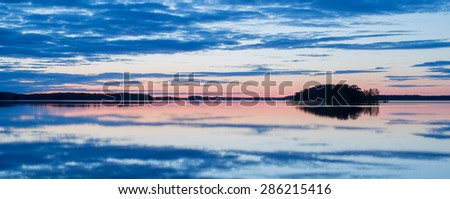 Calm lake reflection at midnight light in Sweden - stock photo