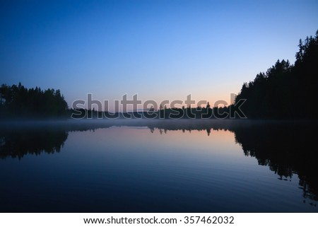 Calm lake scape at summer night in finland - stock photo